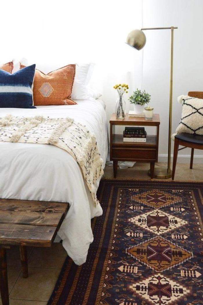chambre à coucher chic ethnique qui combine le blanc, le bleu et les nuances chaudes du marron et de la couleur ocre