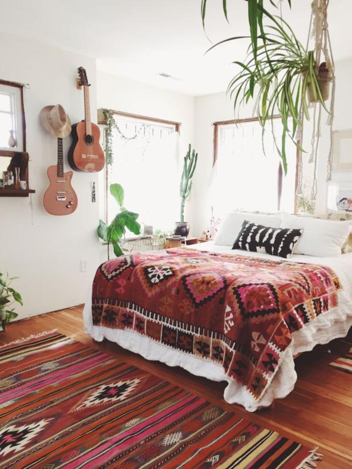 une chambre à coucher bohème chic, un tapis à motif ethnique combiné avec une couverture de mêmes motifs