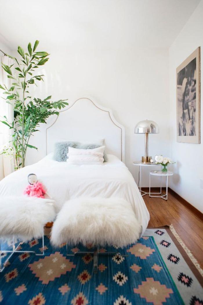 une chambre à coucher élégante en blanc, des tabourets métalliques blancs d'assise en fausse fourrure, tapis ethnique chic bleu