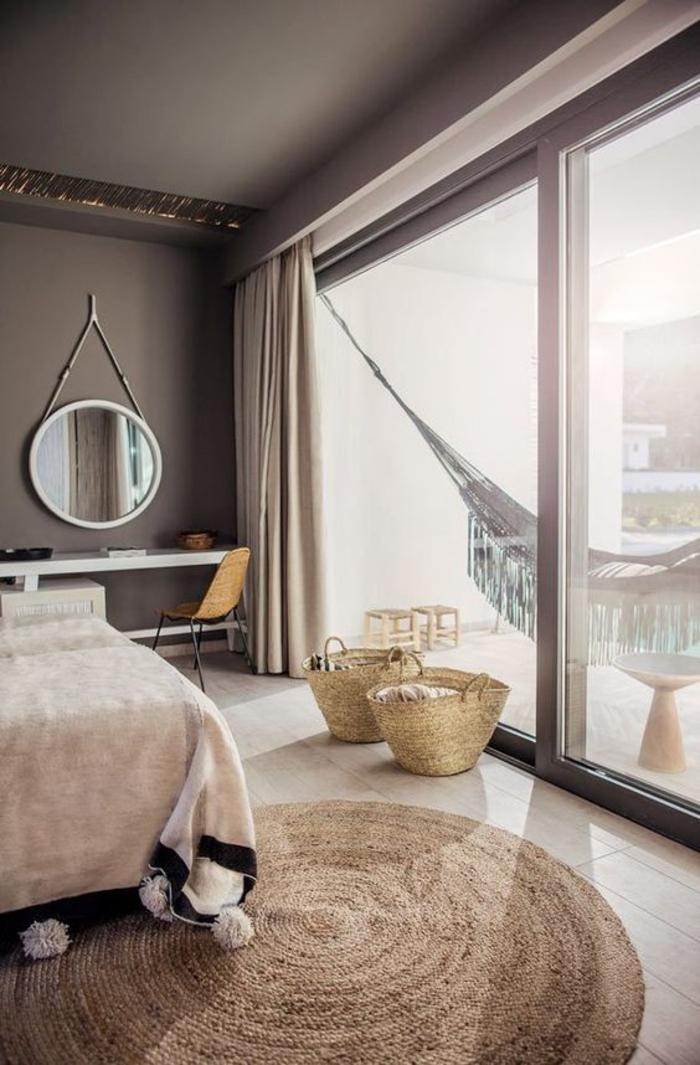 une chambre à coucher aux nuances de beige, un plaid à pompons et un tapis rond en jute