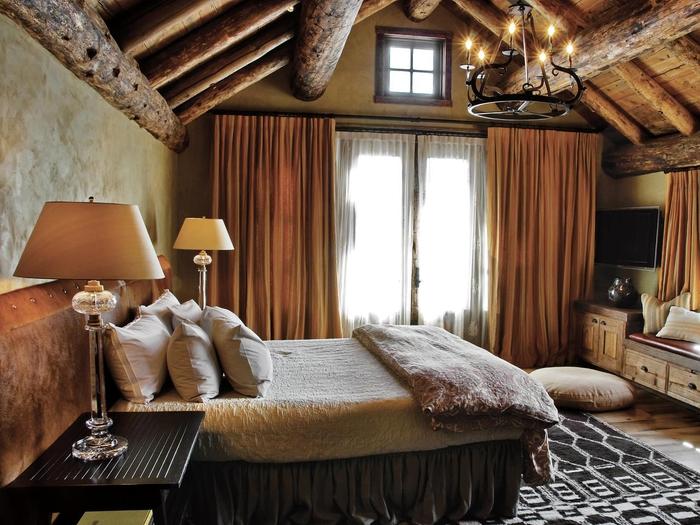 une chambre à coucher rustique aux tons neutres, ambiance de style chalet aux tons neutres, rideaux couleur terre sienne, chambre sous pente aux poutres apparentes en bois rustique