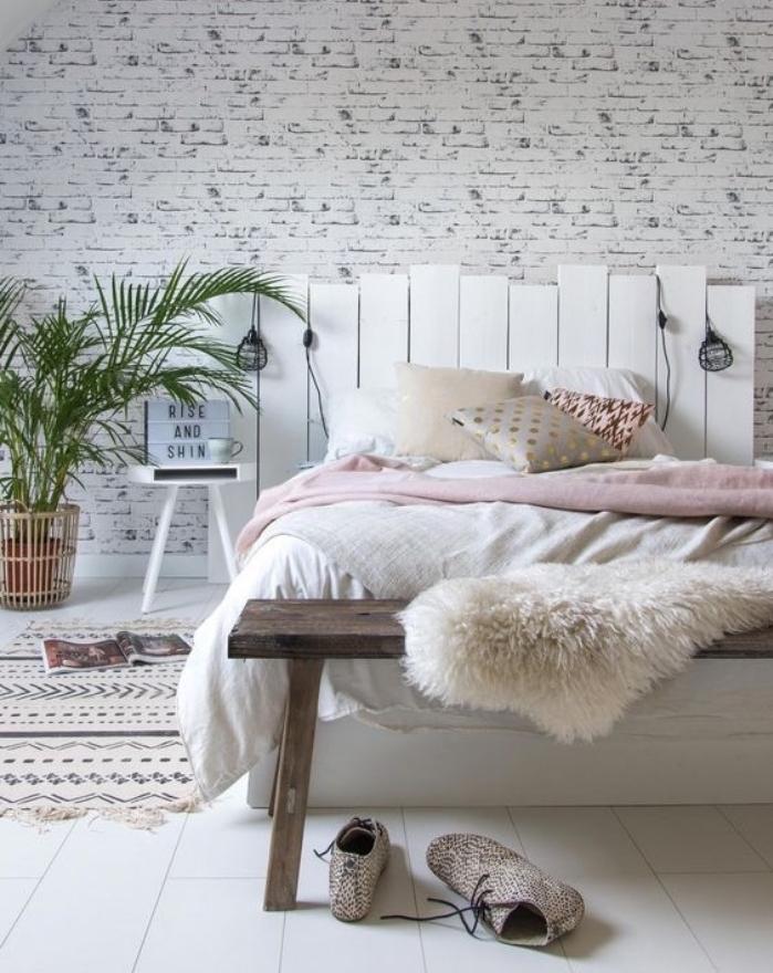 tete de lit en palette démontée, planches de bois repeintes en blanc et linge de lit blanc et rose, coussins multicolores, revetement sol blanc, tapis à motifs géométriques, plantes, lampes