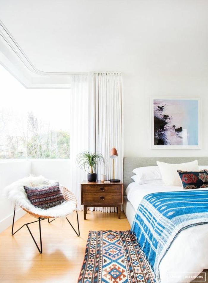 chambre à coucher blanche, tapis ethnique, plaid de lit bleu, peinture abstraite, chaise papasan