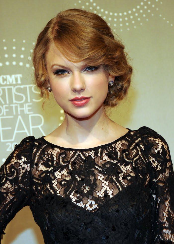 un blond roux sublimé par un chignon bas façon rétro et une robe noire en dentelle