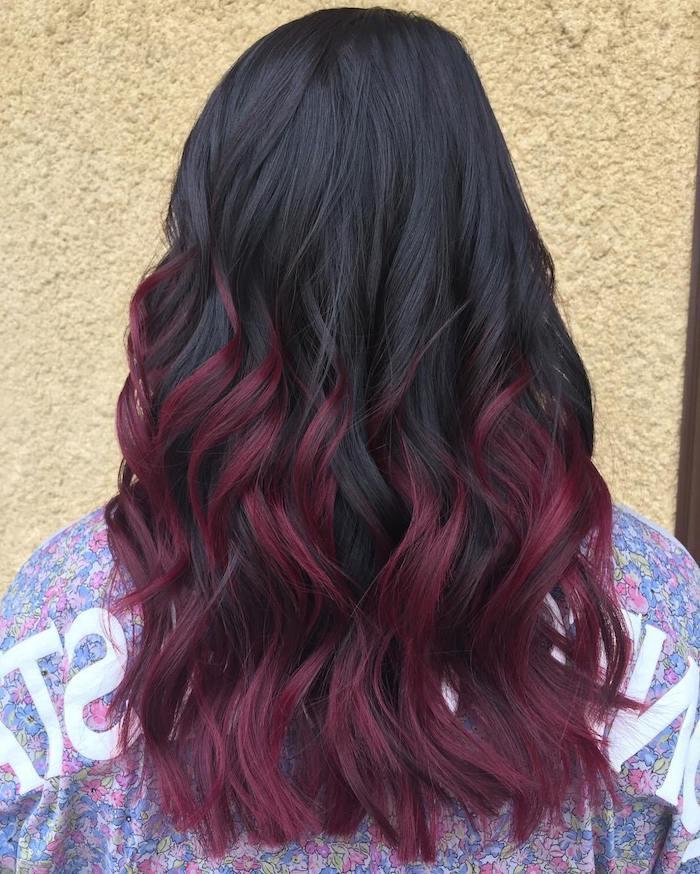 coloration rouge, cheveux noirs avec extrémités en bordeaux, grosses boucles, t-shirt à motifs floraux