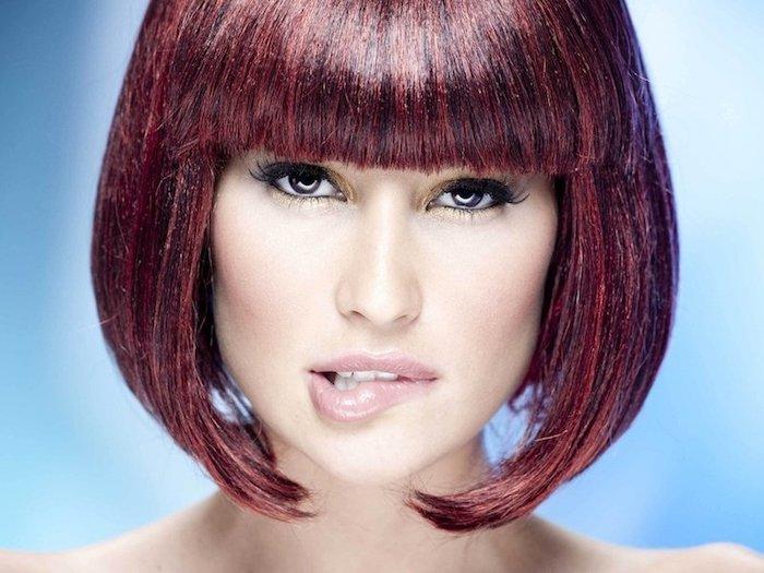 cheveux bordeau, rouge à lèvres -nude, crayon pour yeux nuance dorée, eye-liner noir, coiffure avec frange, coupe carré court