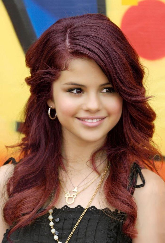 cheveux bordeau, collier en or, robe noire avec boutons, Selena Gomez, coloration rouge foncé