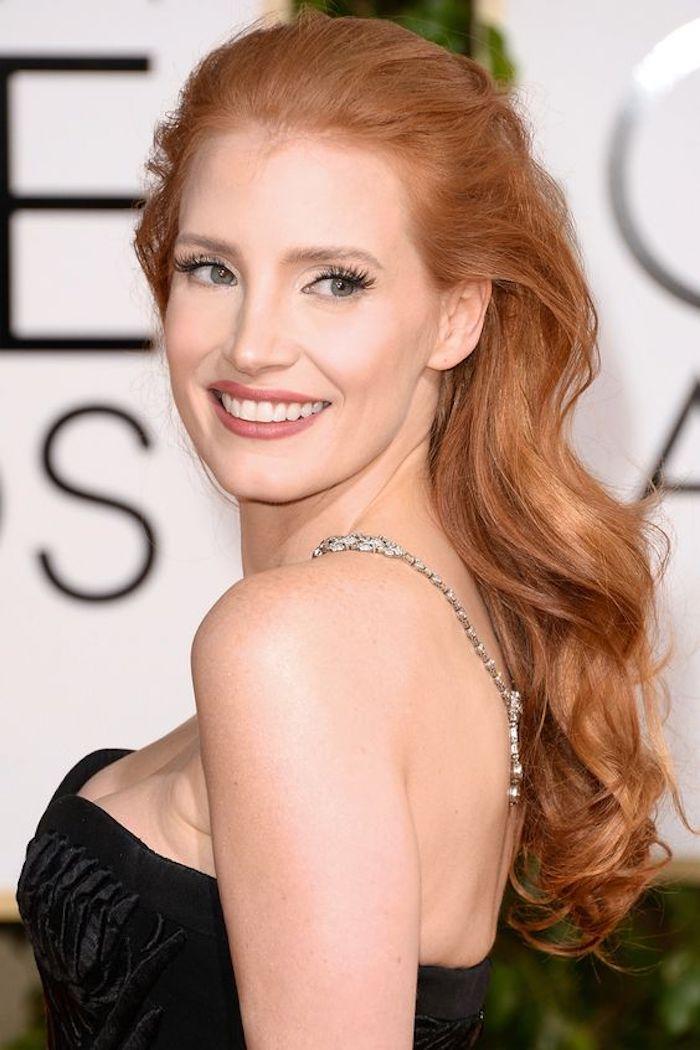 une coiffure sublime de côté, des cheveux roux ondulés aux reflets cuivrés