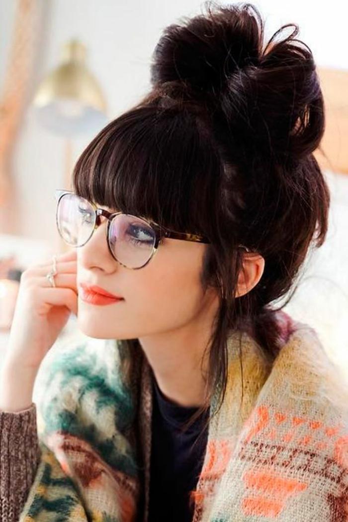 coifure femme ave cheveux en noeud haut sur la tete avec des bangs de coté