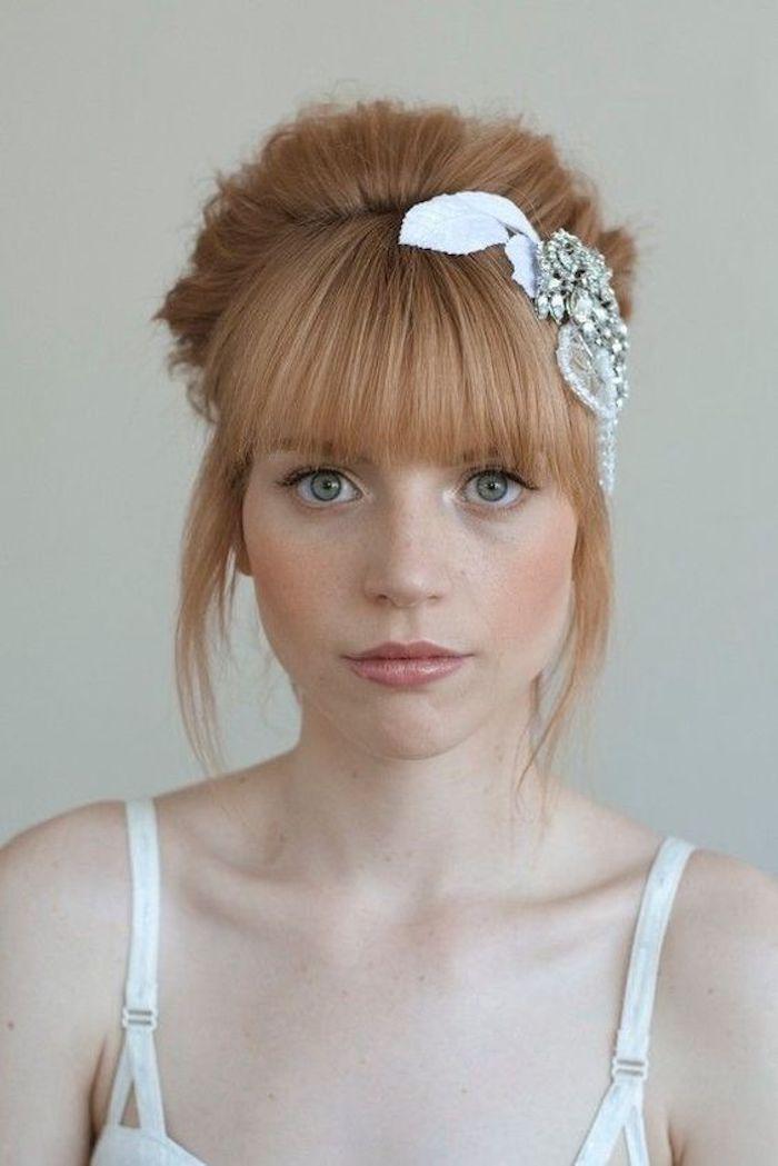 une coiffure de mariée relevée avec frange et joli accessoire avec strass, cheveux blond roux associé à un teint de pêche