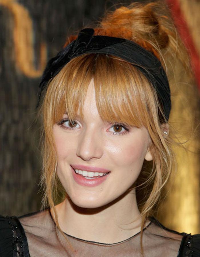 une coiffure relevée girly avec frange et chignon haut flou accessoirisé d'un head band, des cheveux roux vénitien