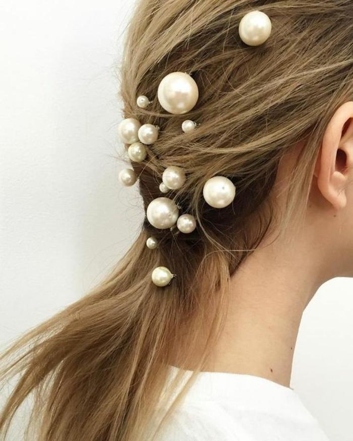 coiffure femme queue de cheval basse ornée de grandes perles décoratives aproppriée pour les mariages et les grandes fetes