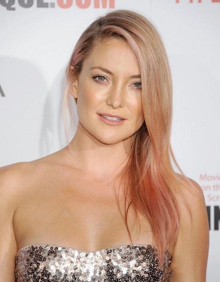 des cheveux couleur blond roux aux mèches roses, coiffure de côté et un maquillage nude subtil