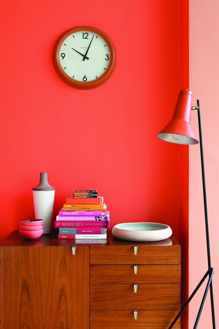 une horloge murale rétro sur un fond corail vif et rose pastel