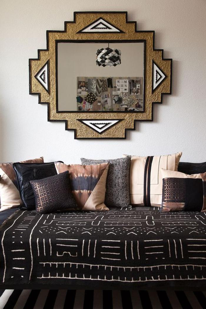 joli miroir à cadre original à motif ethnique, canapé sans dossier décoré de coussins en matière de luxe