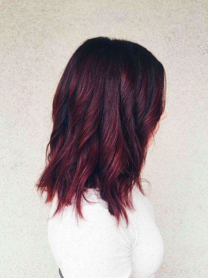 cheveux rouge foncé, blouse blanche, cheveux mi longs, coiffure avec boucles, coloration noir et bordeaux