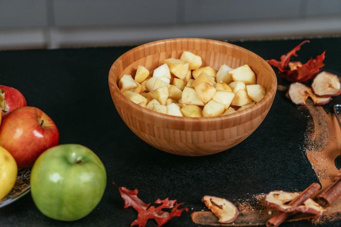 couper les pommes en dés et mettre dans un bol, étape pour faire une tarte aux pommes et épices de noel