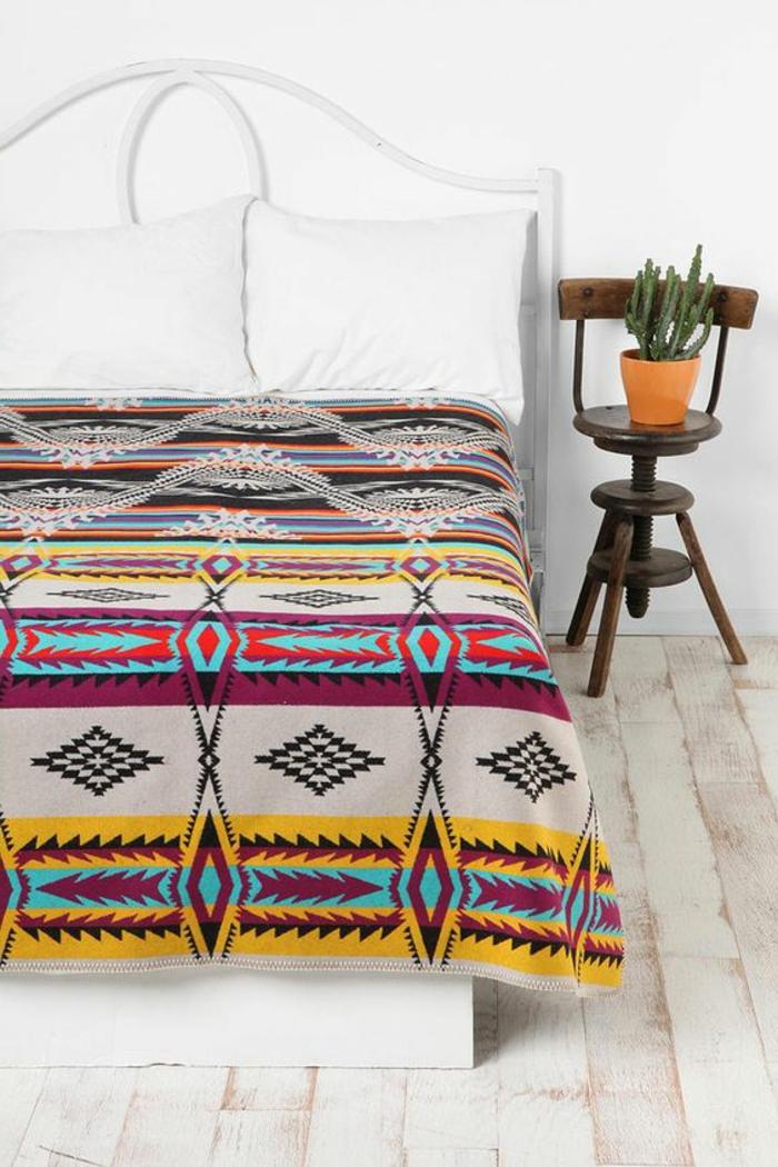 tissu ethnique sur le lit, chambre à coucher blanche, petite chaise rustique en bois
