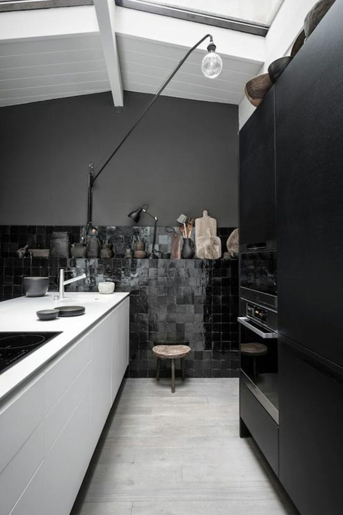 cuisine noire sous toit en pente aux poutres blanches et au mosaique noir foncé sur un mur