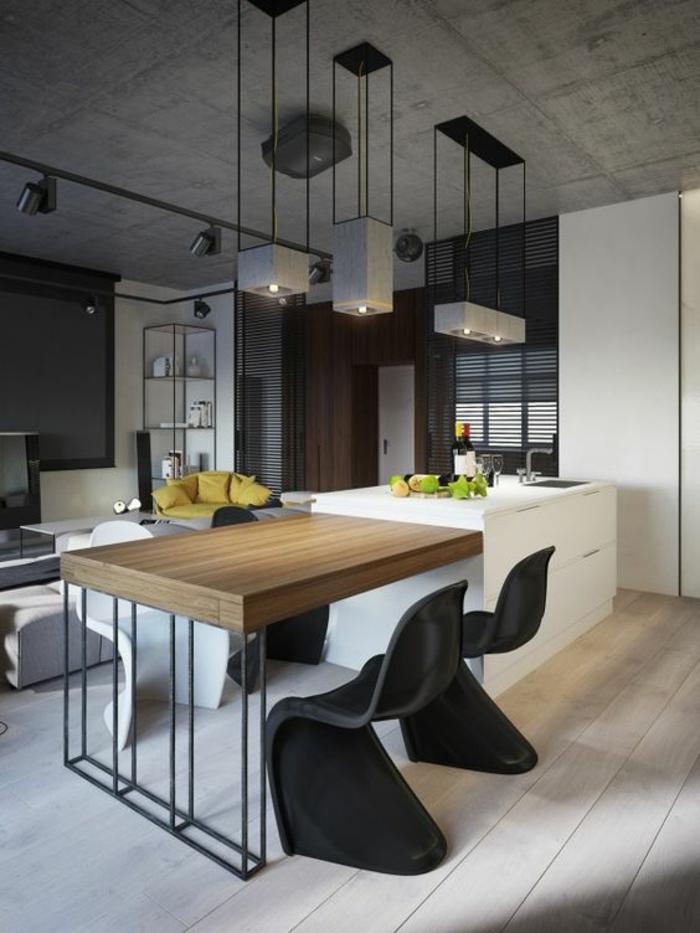 cuisine en noir avec ilot tout blanc et table couleur chatain imitation bois avec des chaises design noires