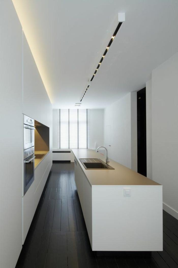 cuisine bois noir pièce en longueur plafond blanc avec des petits luminaires combinés avec lumière jaune incorporée au plafond