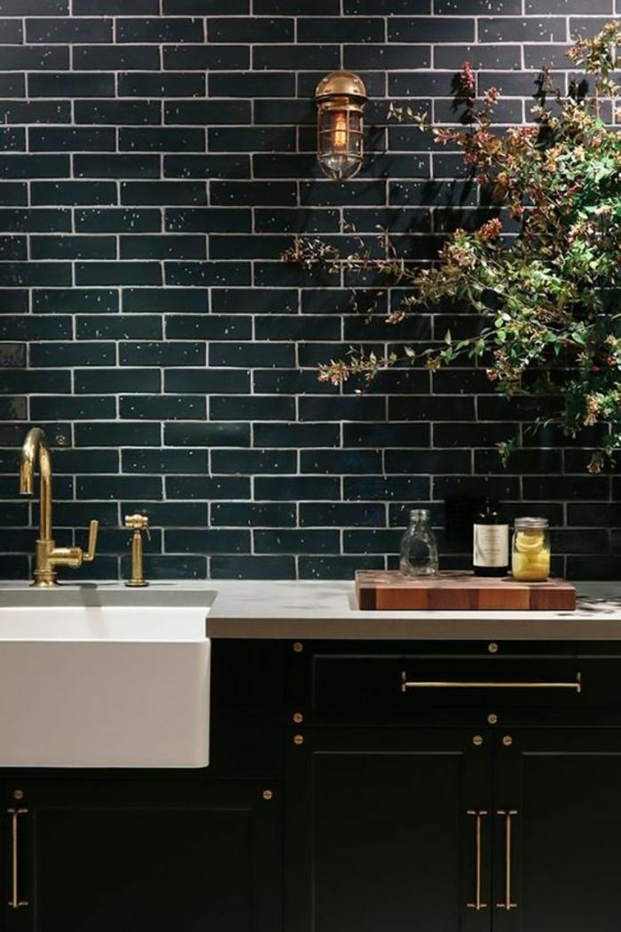 deco cuisine noire avec mur revetu en briques noires polies vasque lavabo blanc évier en métal jaune effet doré