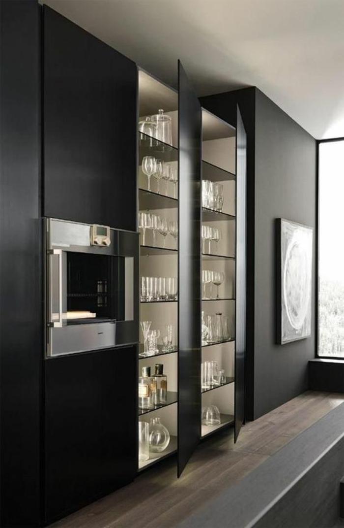 cuisine noir et bois avec des étagères en verre derrière une vitrine en verre blanc