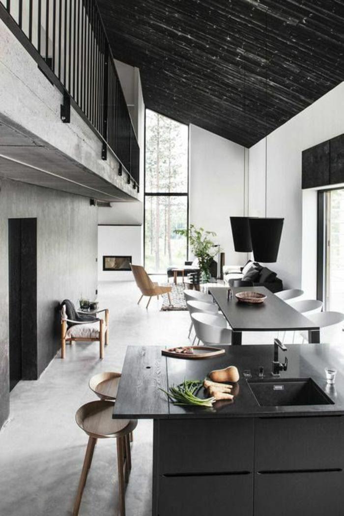 cuisine en noir avec des poutres en noir et une table et un ilot en noir avec le sol couleur taupe