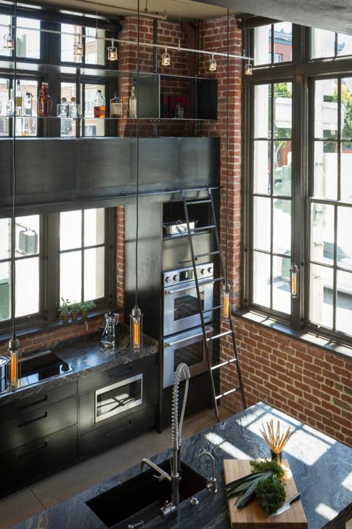 cuisine noire et bois avec des murs en briques rouges plan de travail effet marbre noir