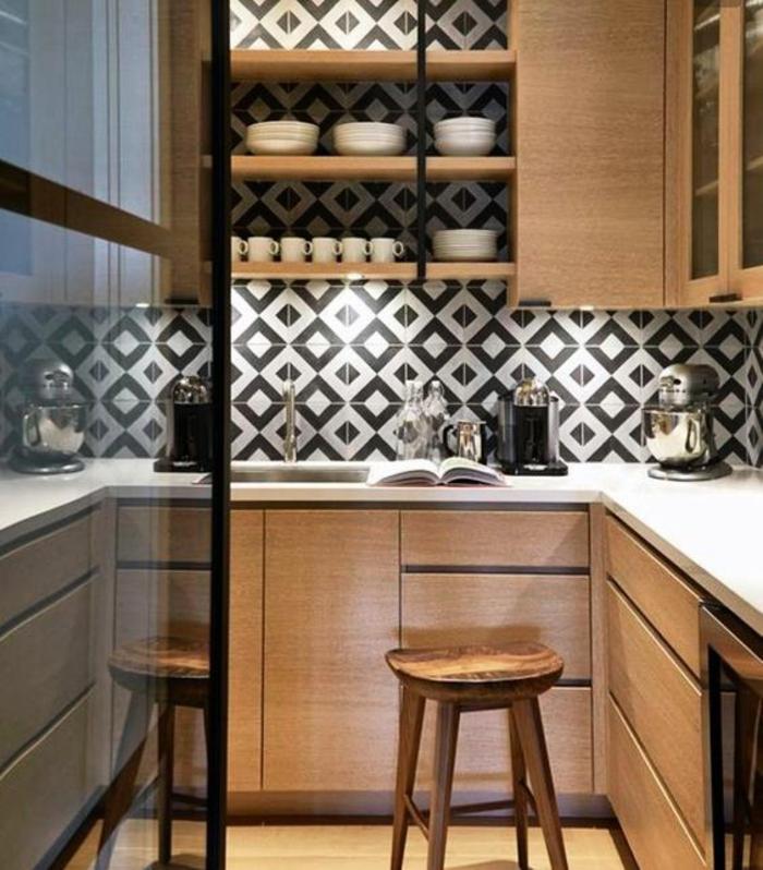 cuisine en noir avec murs revetus en carrelage en noir et blanc aux motifs géométriques
