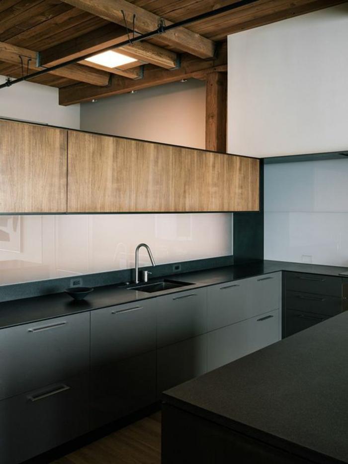 cuisine noir et bois avec des zones imitation bois clair sur les meubles et des poutres en bois clair au plafond