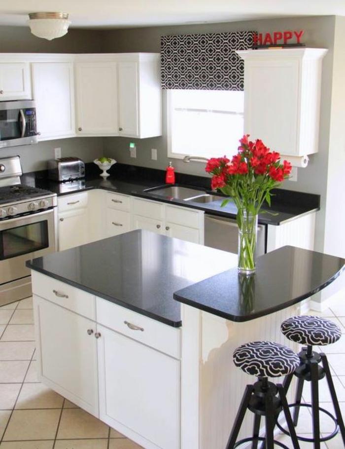 cuisine noir avec des plans de travail noirs disposés sur différents niveaux avec message Happy en rouge sur l'un des meubles