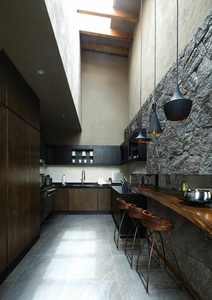 cuisine noir dans un style rustique avec des pierres grises comme revetement sur l un des murs