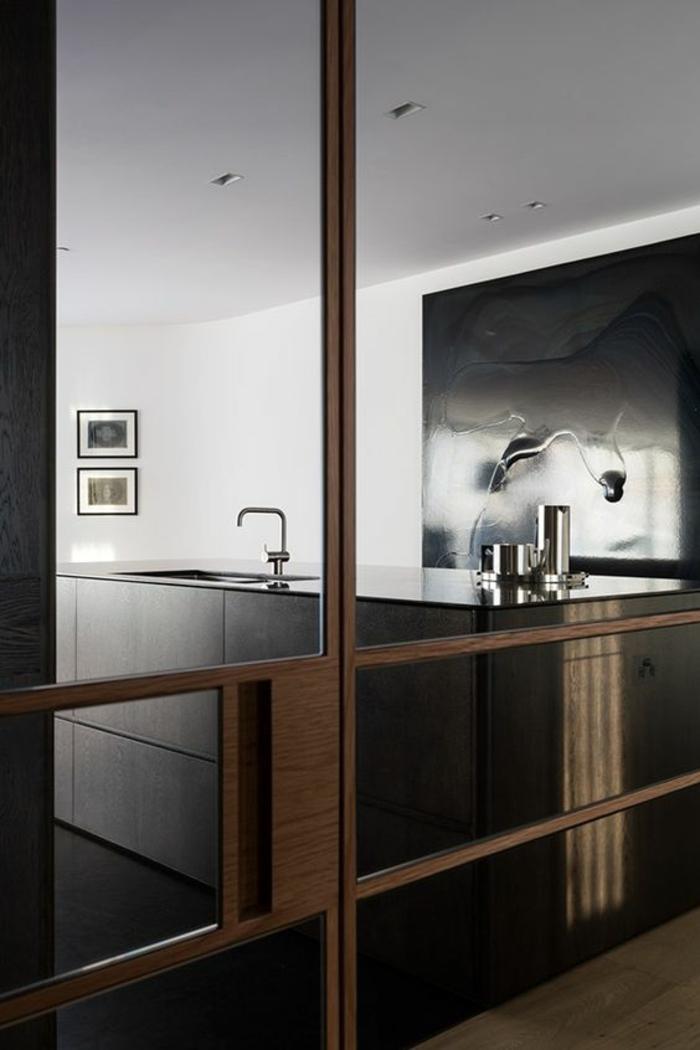 cuisine noir et bois avec ilot au plan de travail en noir et panneau décortif abstrait en noir effet dramatique