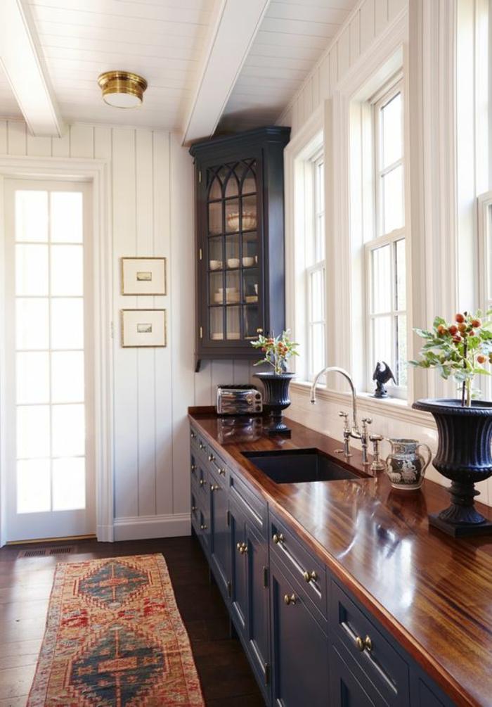 cuisine en noir avec murs et plafond blanc et meuble angulaire pour ranger avec vitrine de style gothique