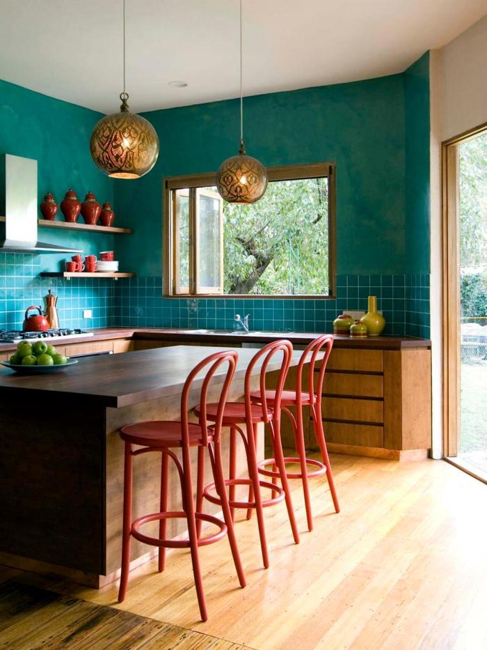 une cuisine éclectique en turquoise équipée d'un îlot de cuisine en bois, des accents déco colorés en couleur de sienne et jaune moutarde, des suspensions boules de style oriental