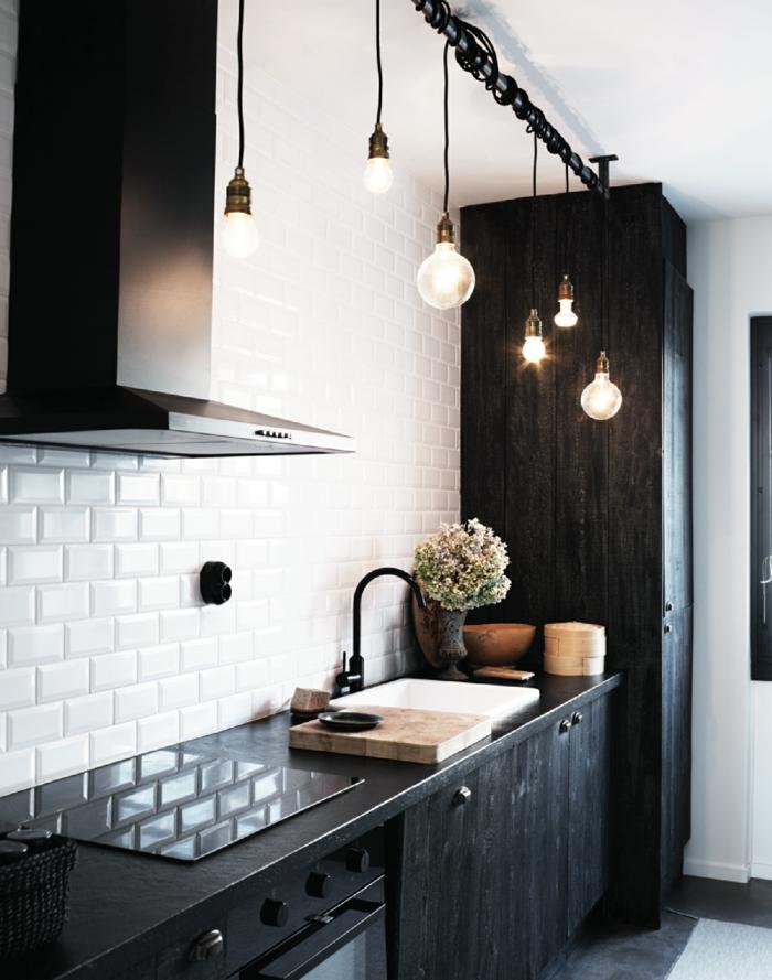 meuble noir et bois, cuisine blanche, corde lumineux, hotte noire, commode de cuisine noire, murs blancs à motifs briques