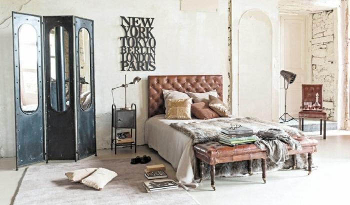 meuble industriel, murs blancs, grand miroir, banc de lit en cuir et bois, livres, linge de lit blanc, coussins décoratifs