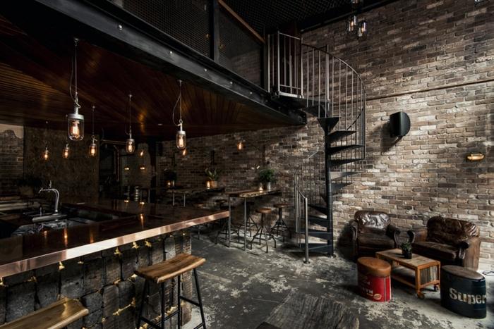 meuble industriel, bar en cuivre, tabouret de bar en bois et fer, plancher gris, lampes suspendues en verre, plantes vertes