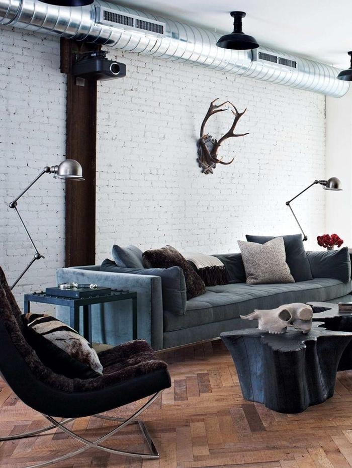meuble industriel, canapé bleu foncé, pipes apparents, coussins décoratifs, lampes en métal, murs en blanc