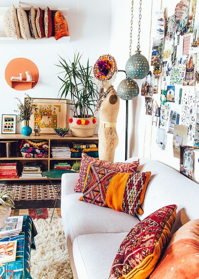 salon à deco ethnique, étagère en bois, plusieurs coussins bariolés, étagères murales