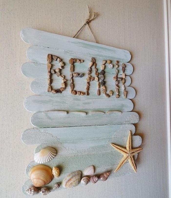 deco bord de mer murale, des batonnets de glace repeints en bleu, mot plage écrit en gravier, étoile de mer et coquillages, bricolage facile