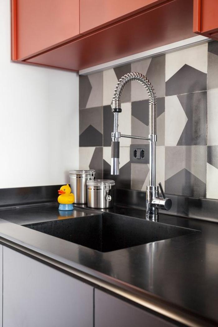cuisine noire avec du gris et du rouge finition tout lisse évier lavabo dans un style industriel moderne