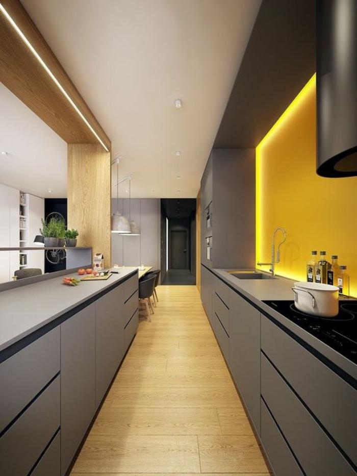 cuisine en noir avec une niche illuminée de lumière jaune plafond partiellement blanc et des accents imitation bois clair