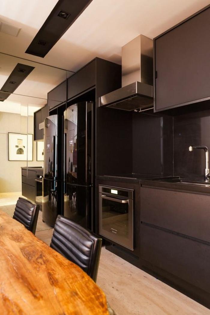 cuisine en noir avec table en bois rude et plafond en blanc et noir avec deux grands frigos