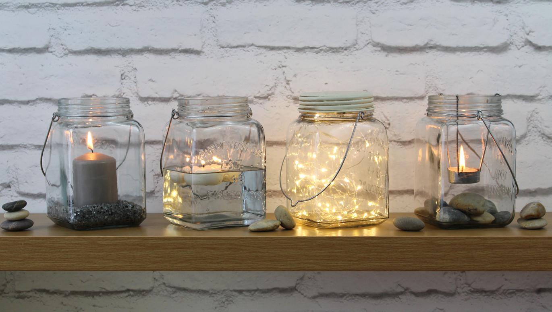 idée deco bord de mer avec des pots en verre, transformés en lanternes, gravier, galets, eau, guirlandes lumineuses, éclairage extérieur romantique, activite manuelle adulte