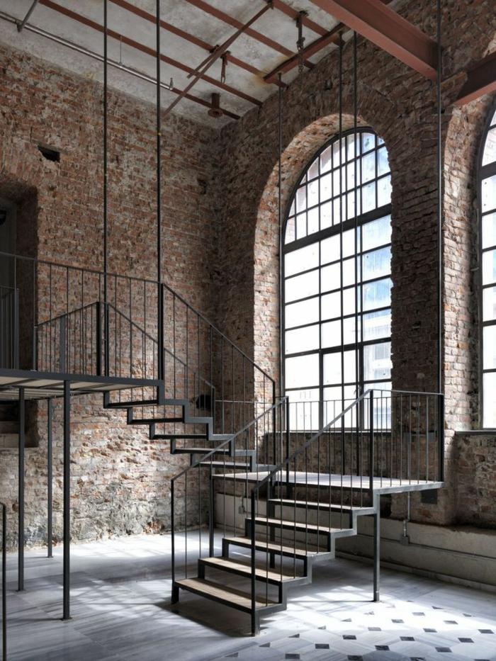 idee deco industrielle, murs en briques, plafond avec poutre, escalier en bois et fer, carrelage blanc et noir, grande fenêtre