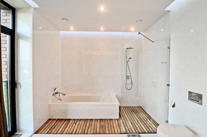 salle de bain moderne, plancher en bois, cuvette wc blanche, murs bancs, plafond suspendu, éclairage led