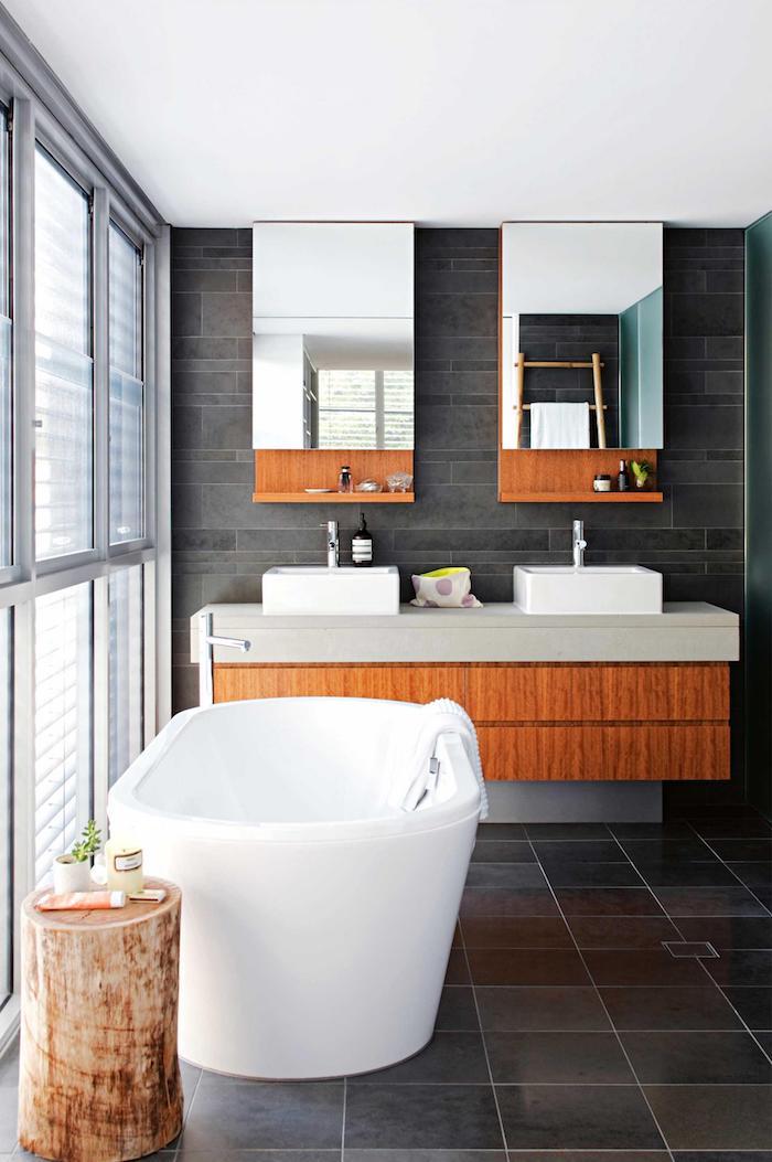 meubles salle de bain, dallage gris, baignoire céramique, petite table en bûche de bois, stores blancs
