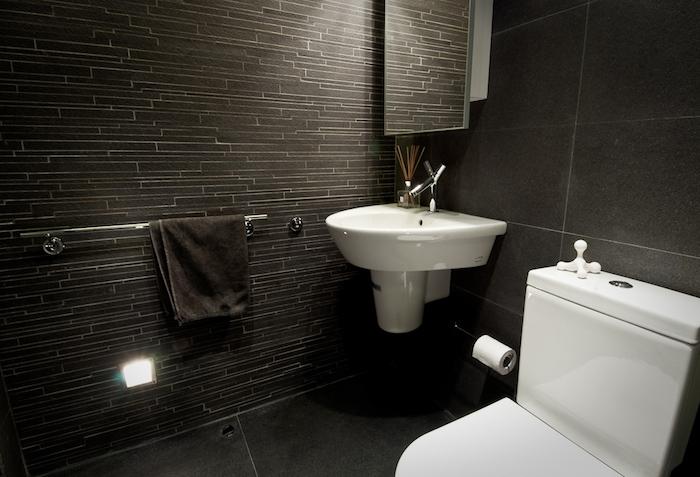 salle de bain design, serviette noire, mur gris foncé, robinet en acier, cuvette wc blanche